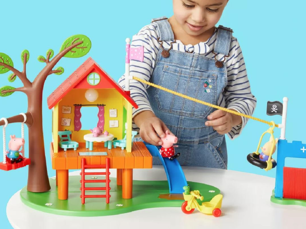 little girl playing with plastic treehouse set