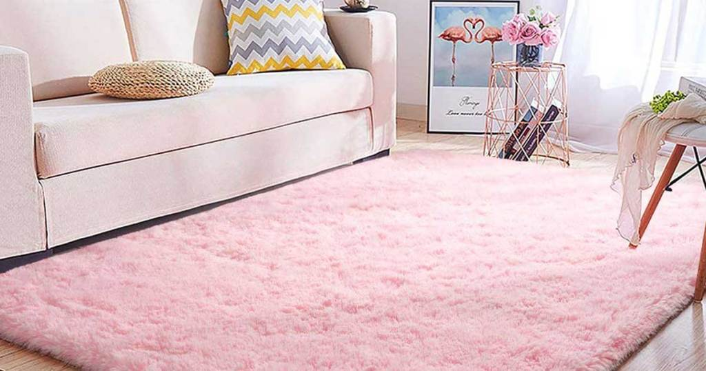 nursery with a big pink soft rug in the middle of it