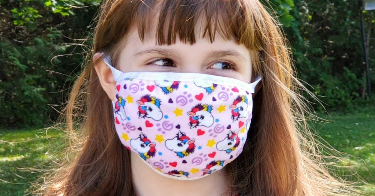 close up of girl wearing a unicorn print face mask