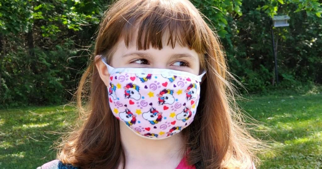 girl wearing a unicorn print face mask standing outside