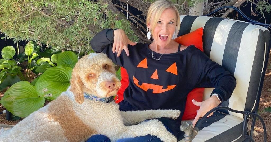 woman wearing pumpkin shirt sitting next to dog