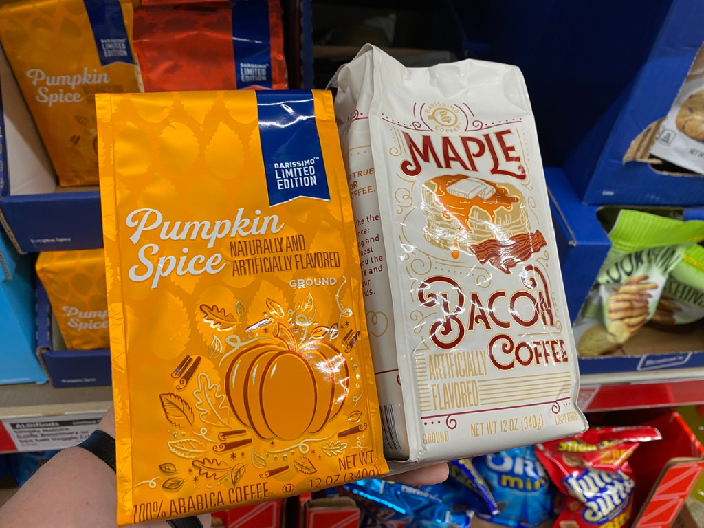 hand holding up 2 bags of fall flavored coffee in store