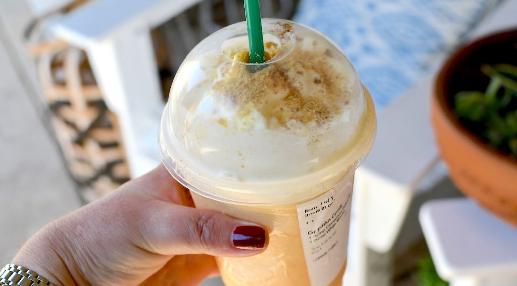 hand holding starbucks pumpkin frappuccino in hand