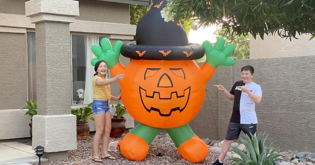 kids next to orange inflatable pumpkin with hat for pumpkin extravaganza giveaway