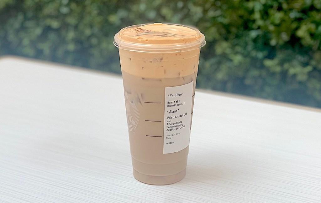 starbucks pumpkin king iced chai latte sitting on white table outside