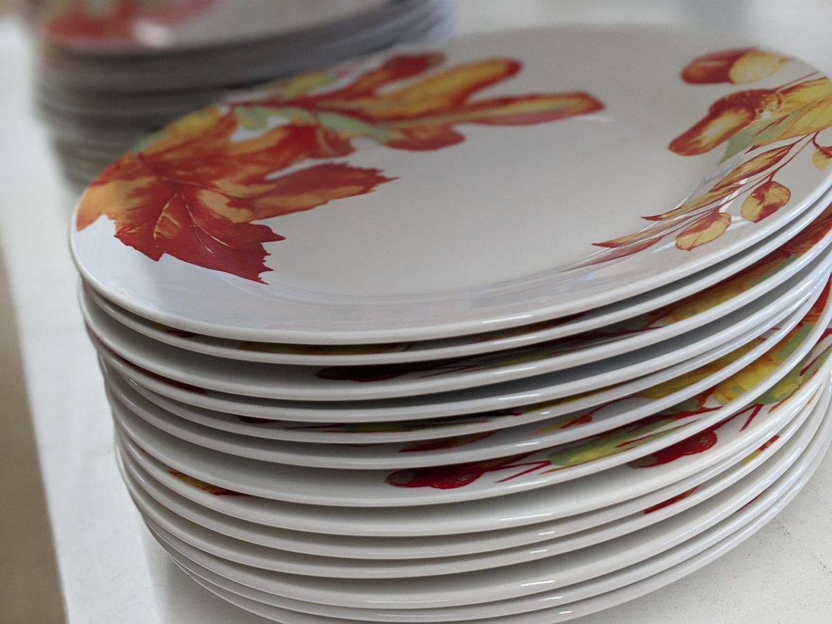plates stacked up in store with leaves painted on them