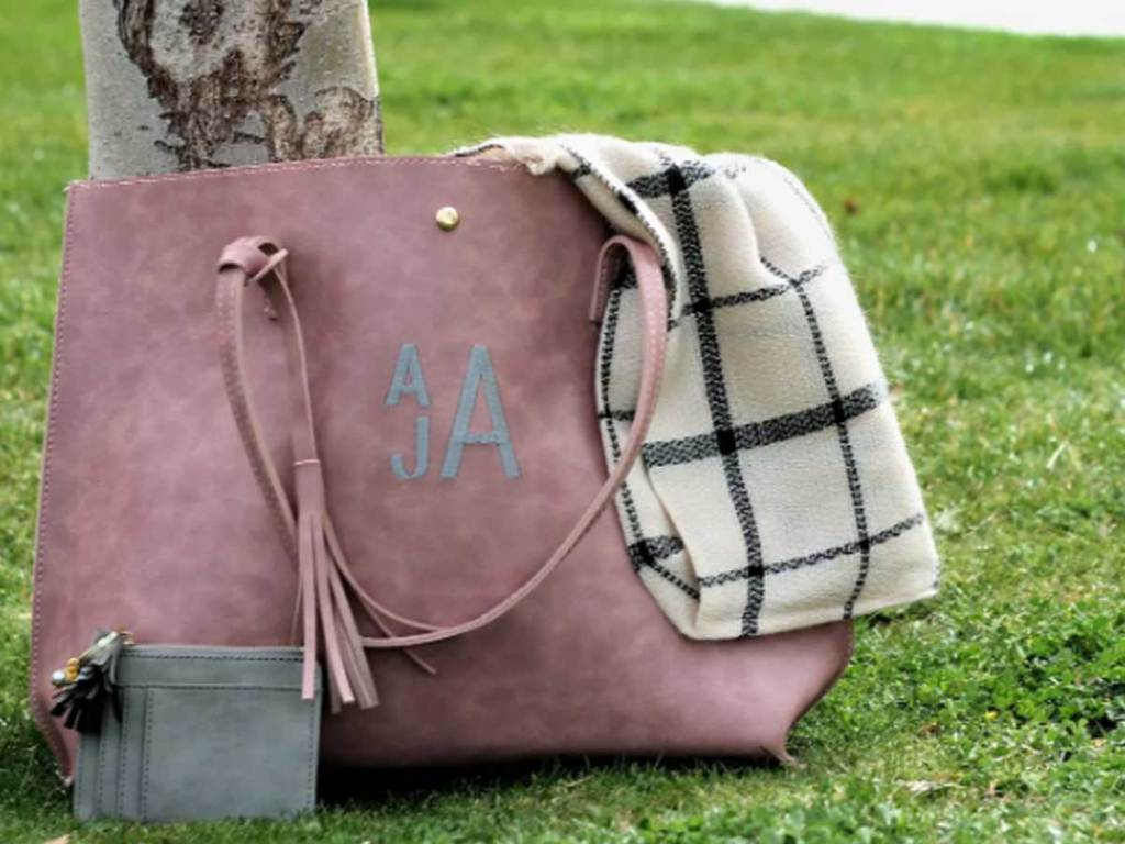 leather like tote bag with monogrammed outside on grass