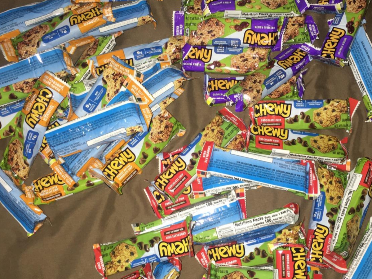 lots of packaged granola bars on bed