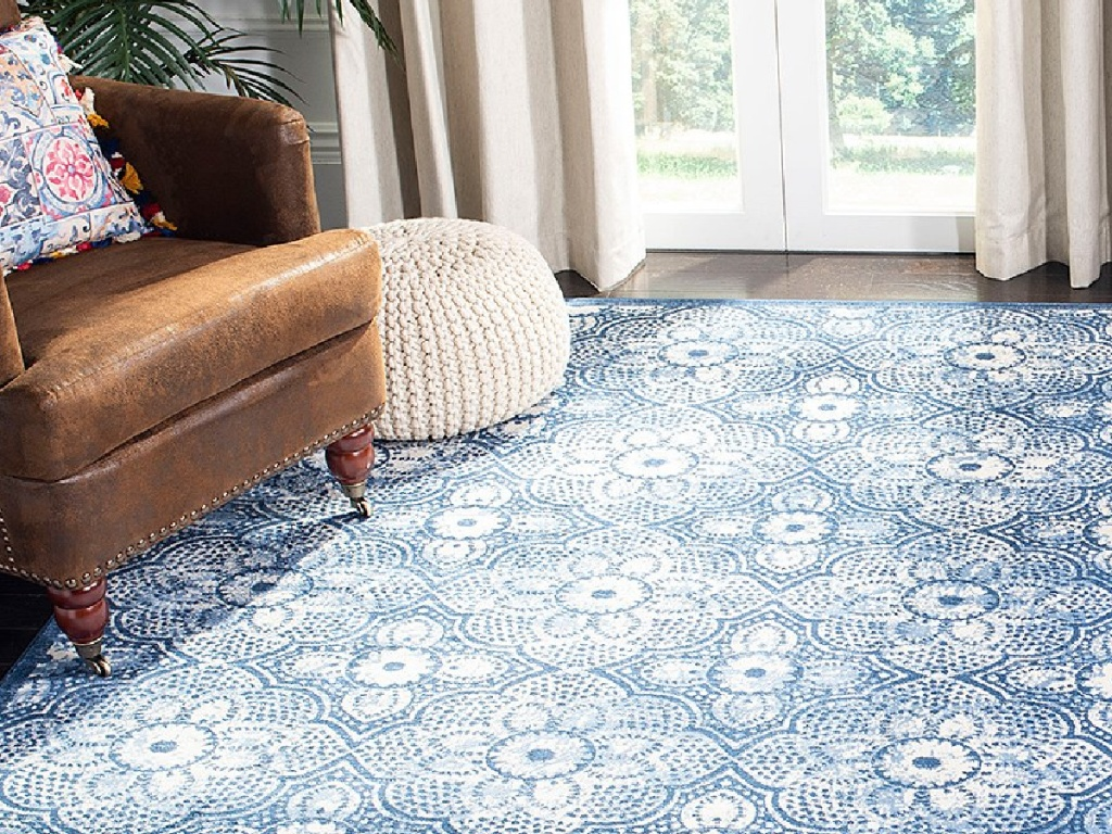 blue and white floral area rug in a living area with a brown leather chair and cream colored ottoman