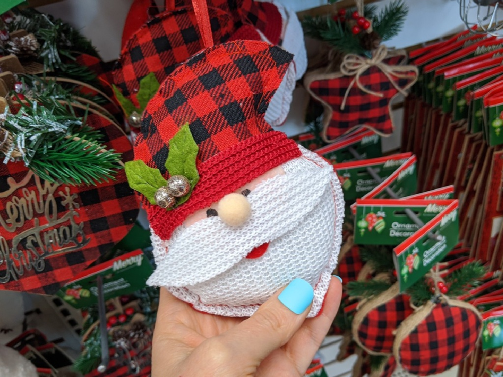 hand holding plush ornament in store that looks like Santa