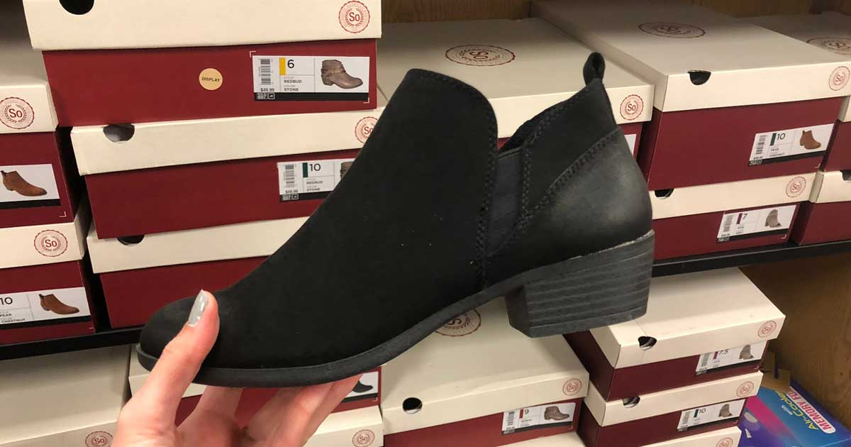 hand holding a black ankle boot in store