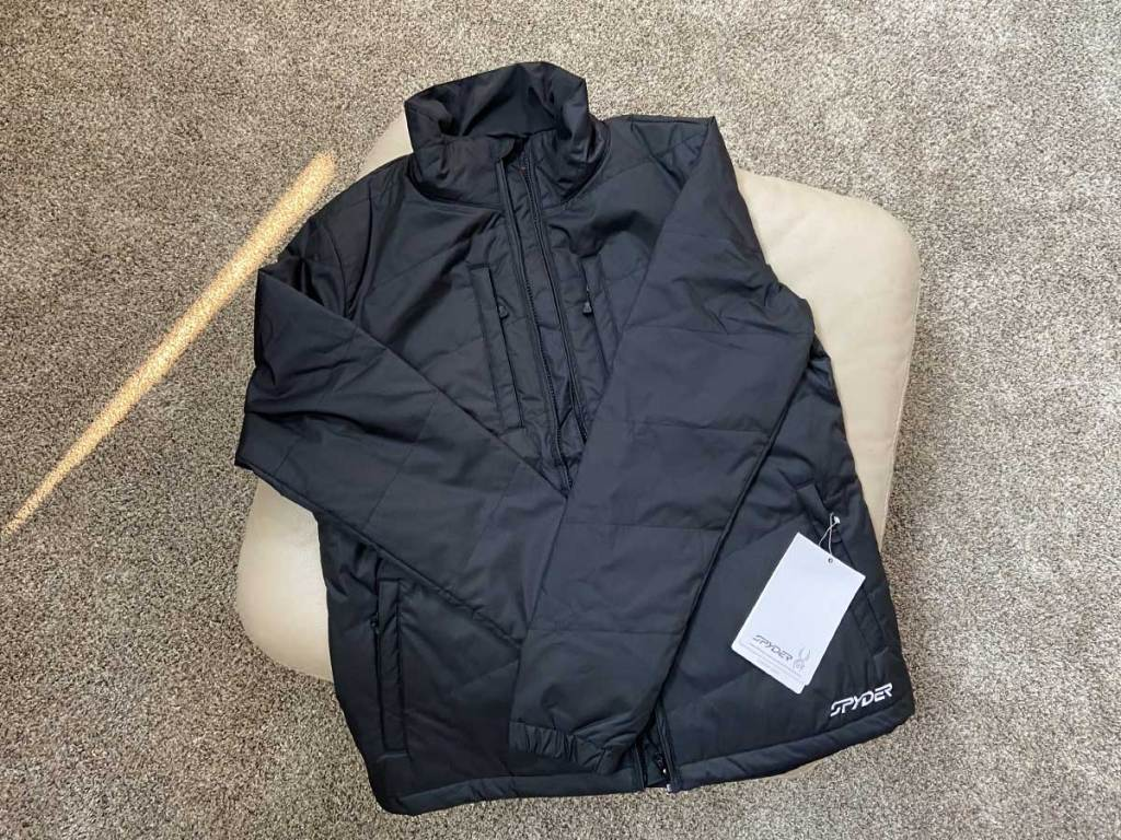 black winter jacket laying folded on the floor