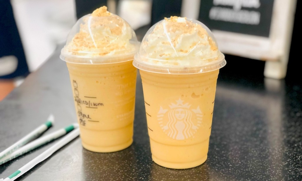two starbucks pumpkin cheesecake frappuccinos sitting on counter