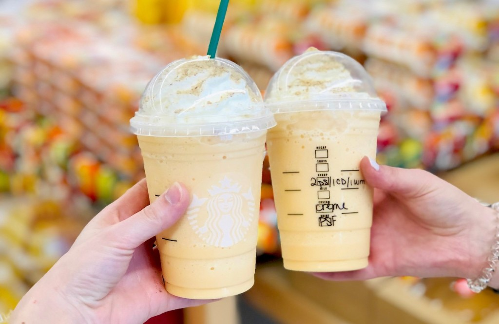 two hands holding up starbucks pumpkin frappuccino drinks