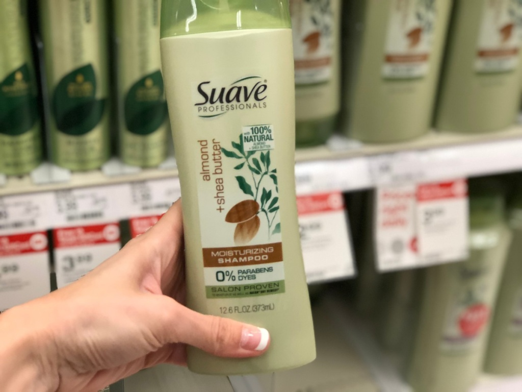 hand holding bottle of shampoo by store display