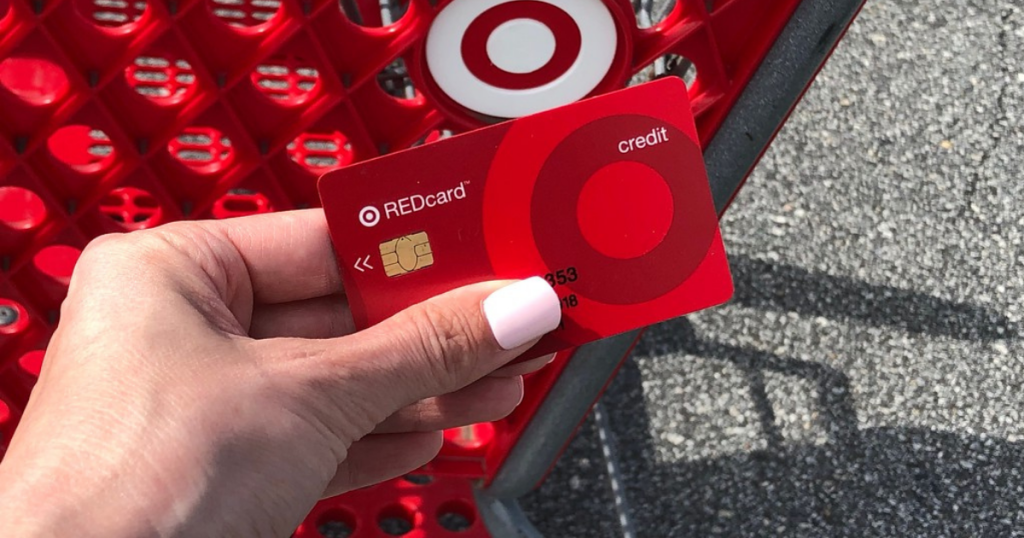 woman's hand holding a target redcard above a target shopping cart