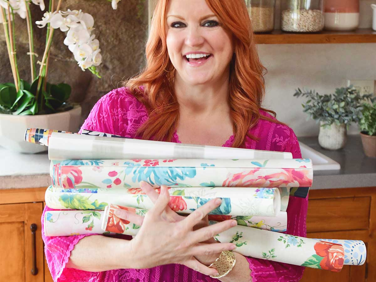 a lady holding rolls of wall paper