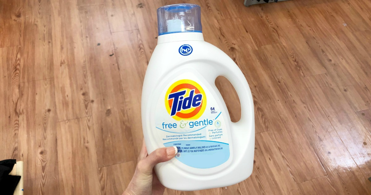 hand holding a bottle of tide laundry detergent above a polished wood floor