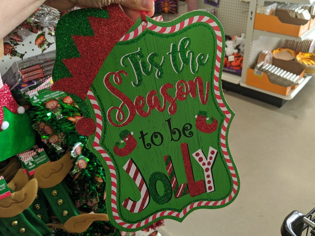 """hand holding up wooden sign that says """"tis the season"""""""