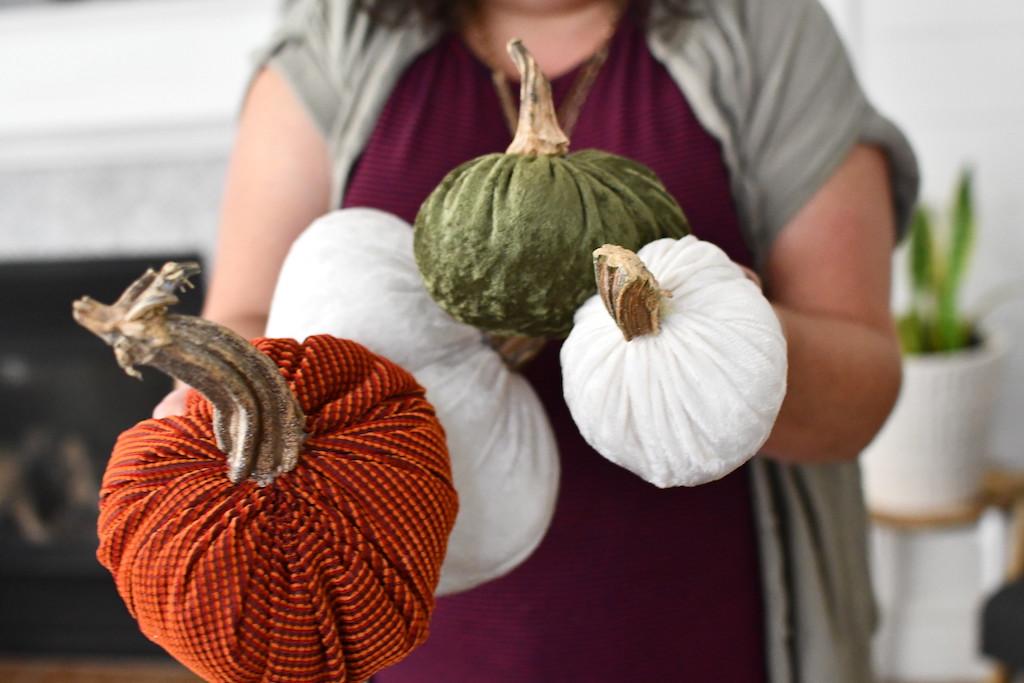 woman holding velvet pumpkins