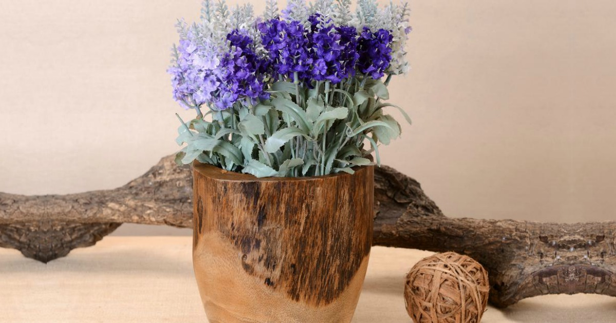 wooden vase filled with purple flowers set in front of a piece of driftwood