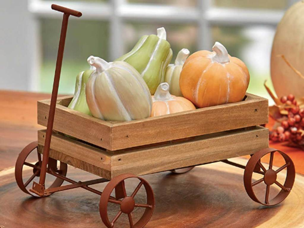 wooden wagon and pumpkins on a table