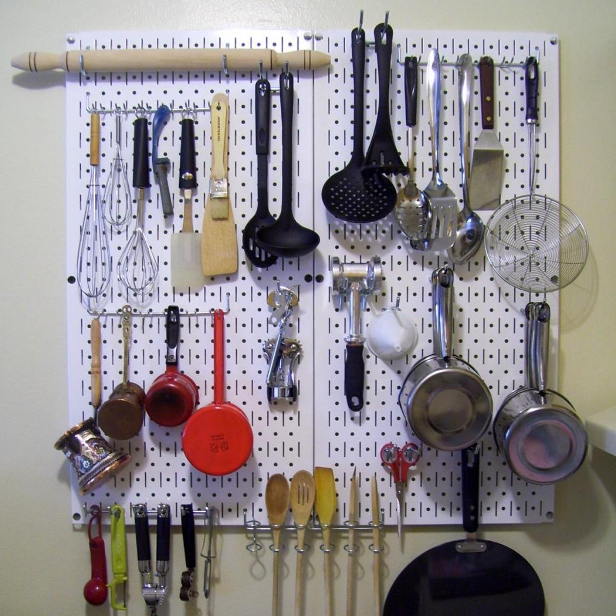 kitchen utensils hanging on white pegboard
