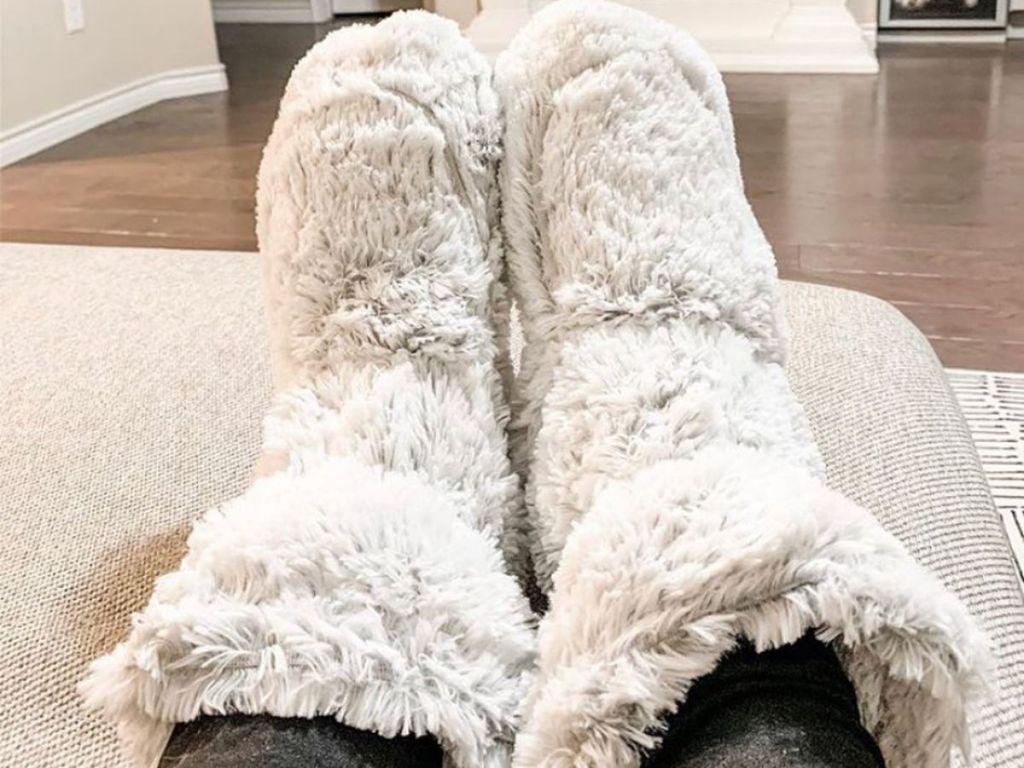 woman resting feet on ottoman wearing warmies plush boots