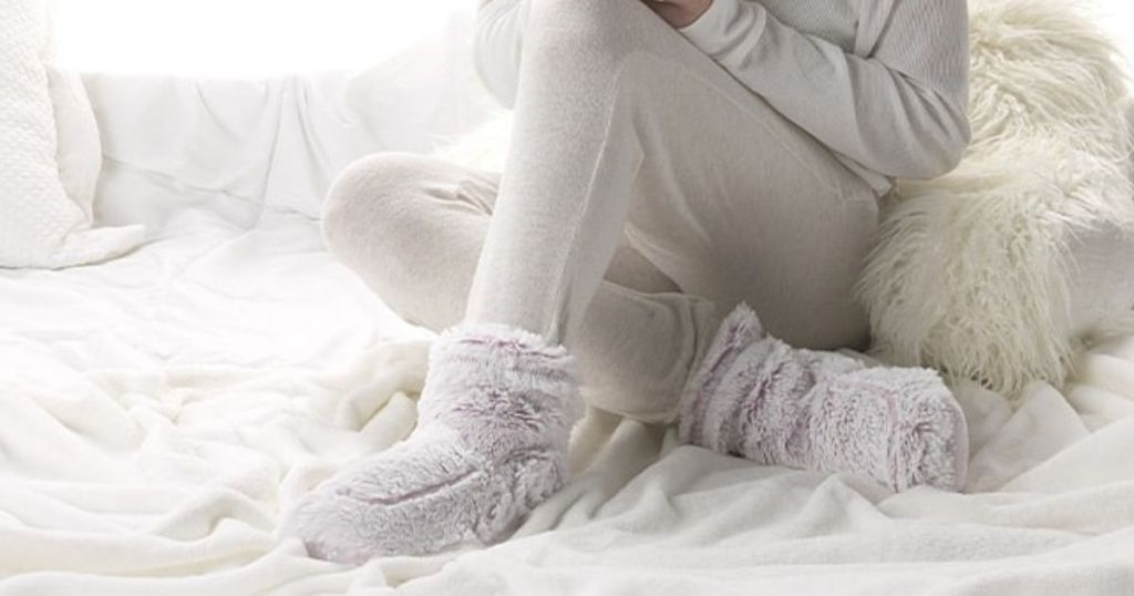 woman sitting in bed wearing plush booties