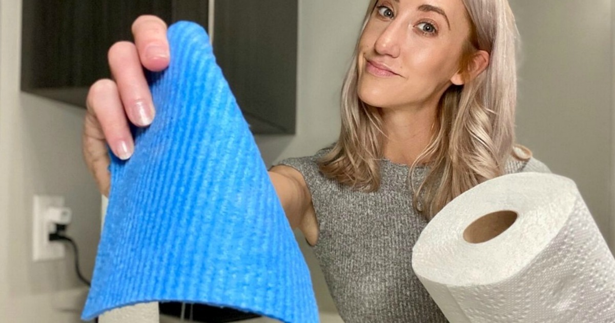 woman holding Swedish dishcloth and paper towels