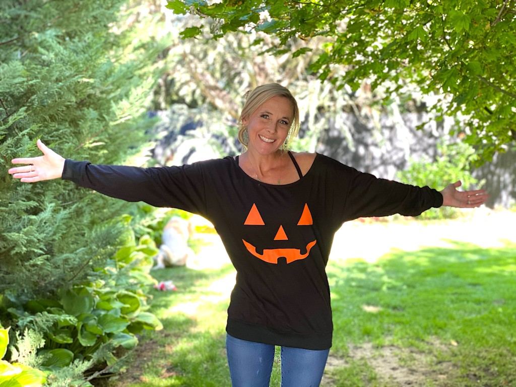 woman in pumpkin sweatshirt with arms out outside