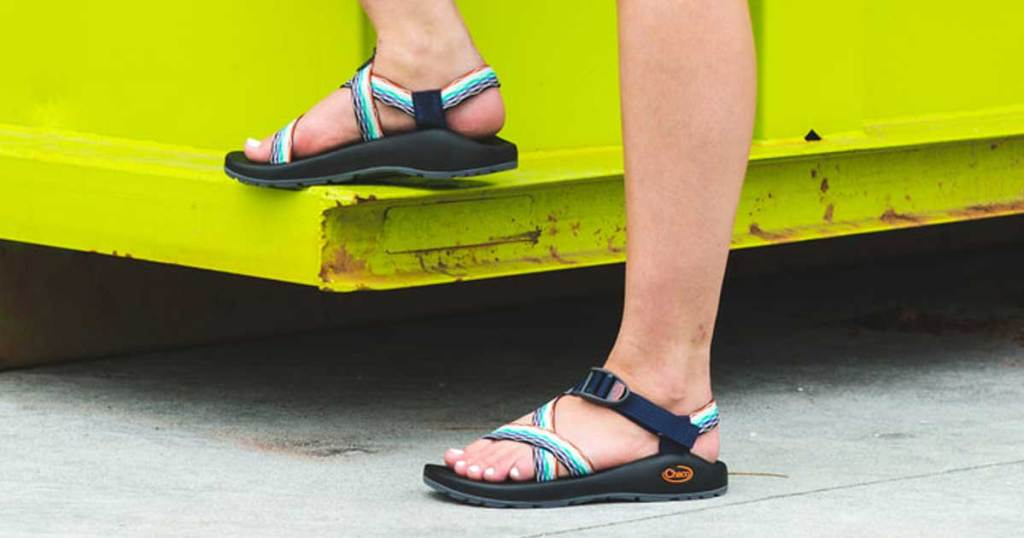 woman wearing sandals with straps near a truck