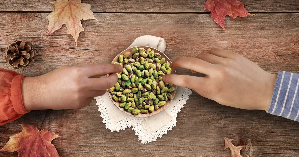 hands grabbing pistachios out of bowl on wood surface with fall leaves around
