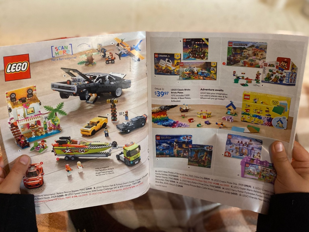 child holding the walmart 2020 toy catalog open to a lego page