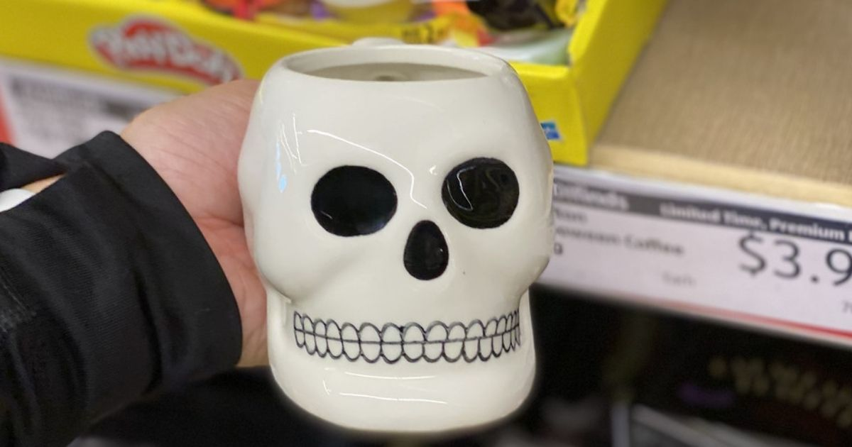 hand holding an ALDI Skeleton Head Coffee Mug in store