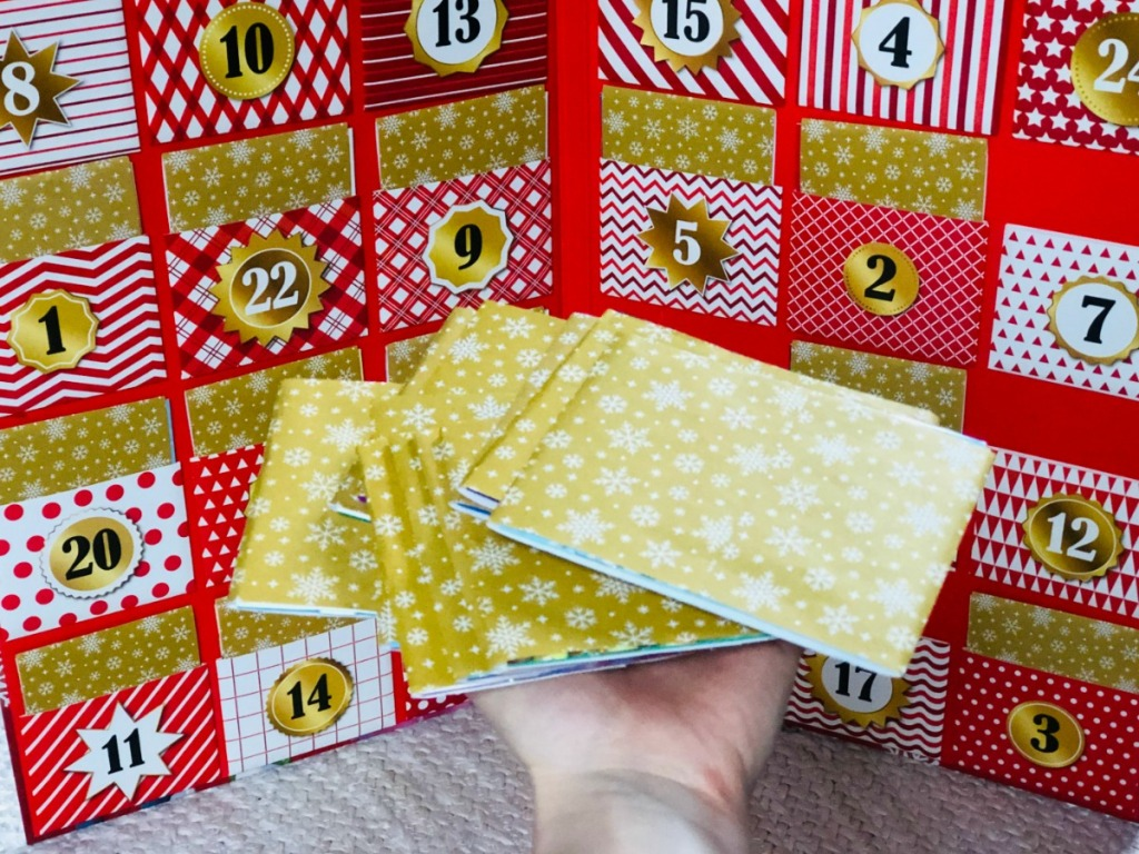 person holding gold-wrapped advent calendar books