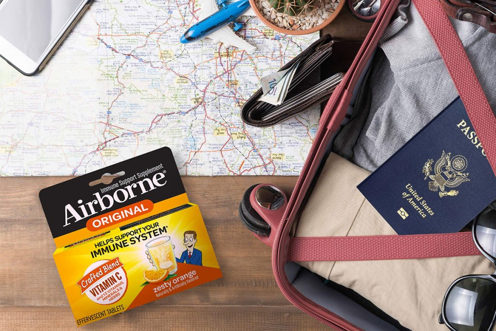 box of orange airborne tablets next to map, suitcase, and passport