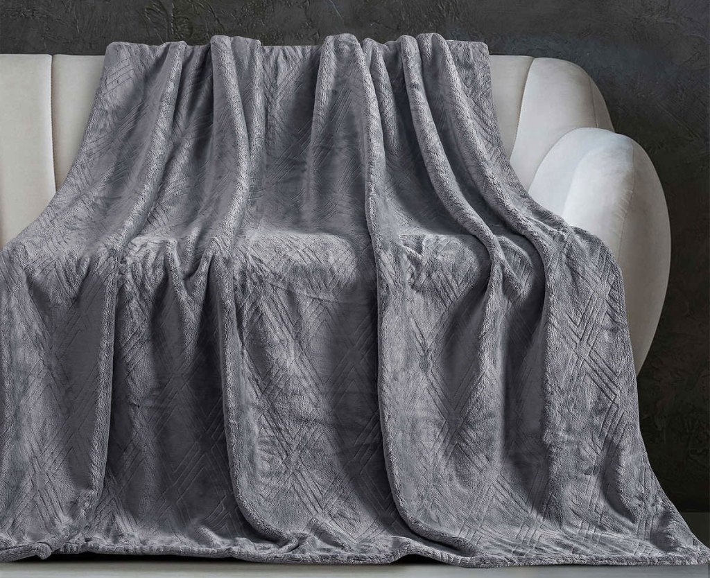 grey embossed velvet throw blanket draped over a couch