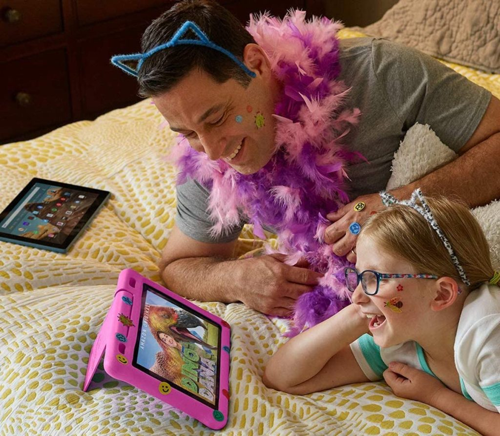 dad and daughter laying on blanket watching pink amazon fire kids tablet