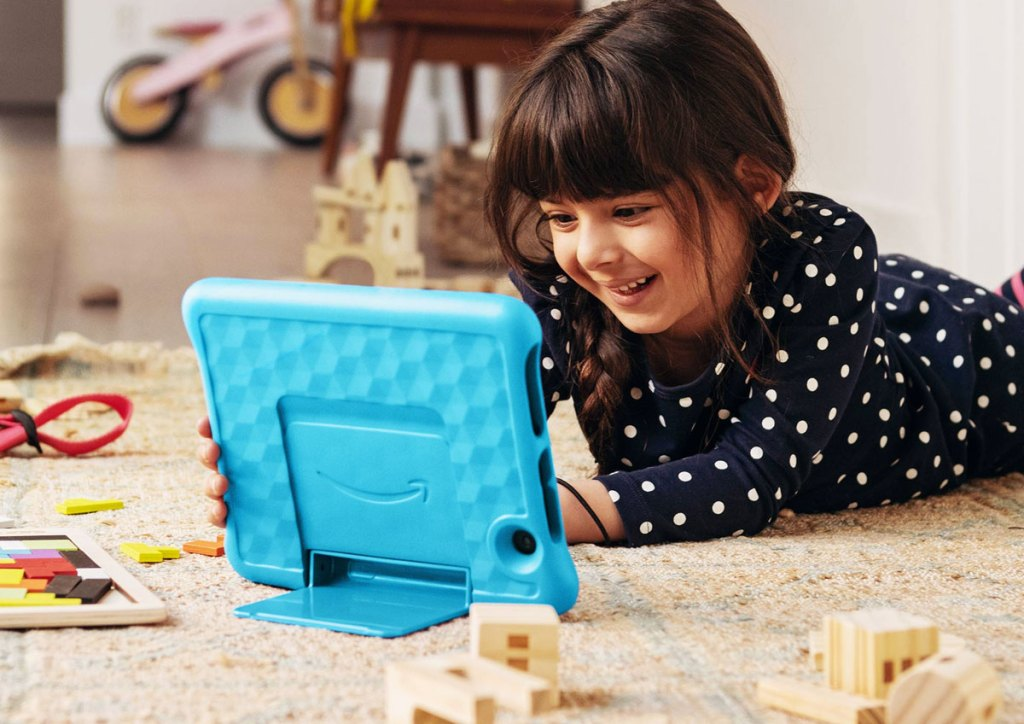 girl laying on floor playing with an amazon fire kits tablet with blue case