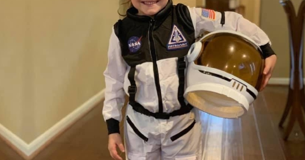 child wearing an astronaut costume holding the helmet