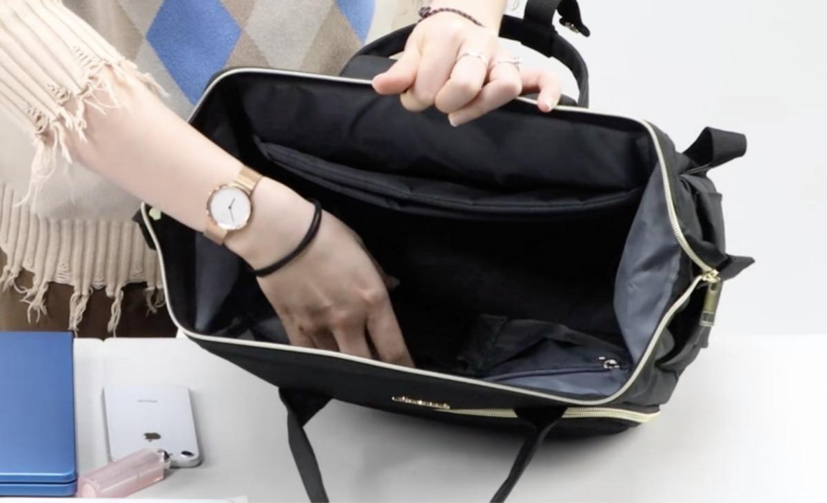 Woman's hand reaching into a black purse