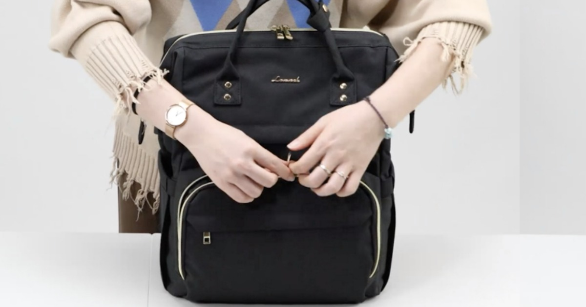 Woman closing a small black laptop backpack
