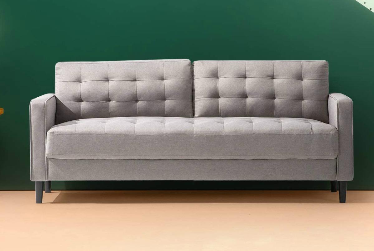 large gray sofa on a hardwood floor near a green wall
