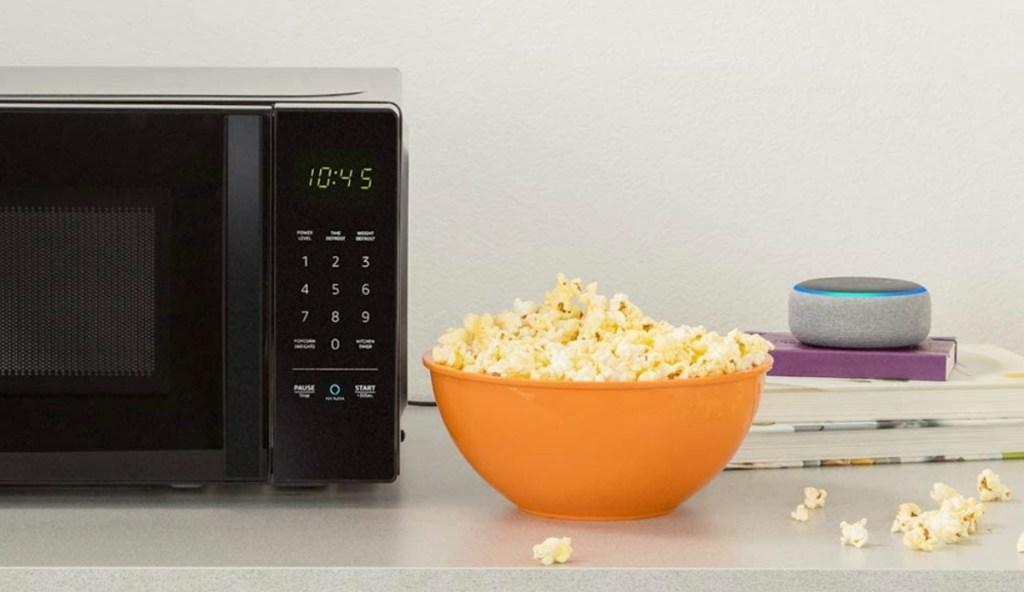 Small black microwave near a bowl of popcorn