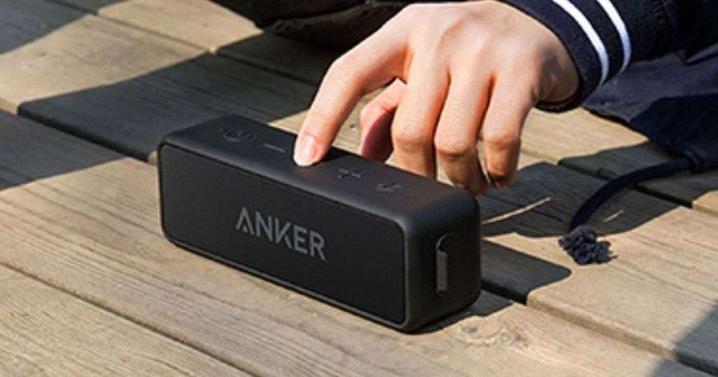 hand pushing play on Anker Soundcore 2 Portable Bluetooth Speaker
