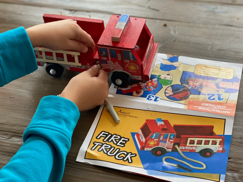 child's hand building a red wood fire truck