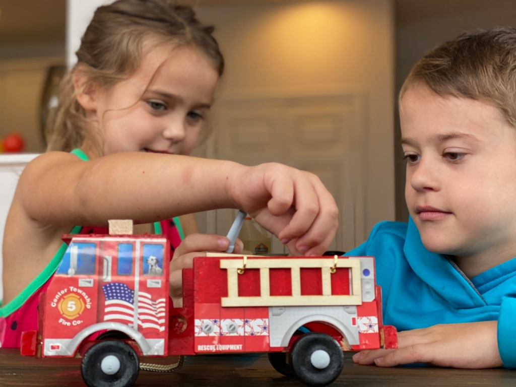 2 children playing with a red fire truck