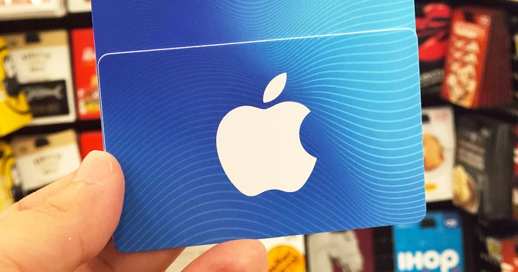 person holding up a white and blue apple gift card