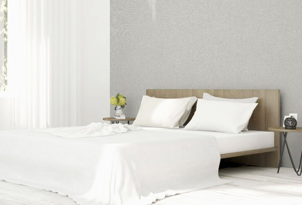 light grey textured wallpaper on wall behind bed with white linens